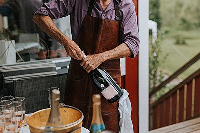 Man opening champagne bottle - p312m2191150 by Jennifer Nilsson