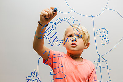 Boy drawing with marker pen onto glass wall - p429m1504957 by JFCreatives