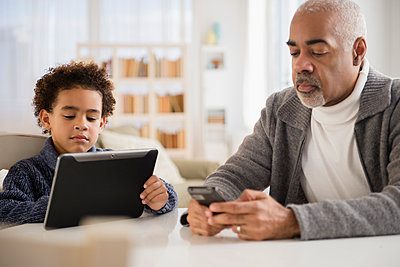 Mixed race grandfather and grandson using cell phone and digital tablet - p555m1413052 by JGI/Jamie Grill