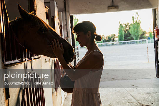 Woman stroking horse in stable