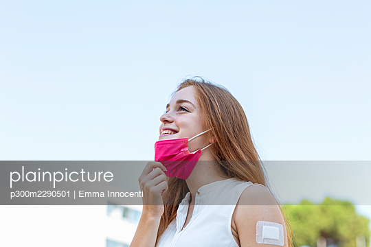 Smiling female freelancer removing protective face mask during pandemic - p300m2290501 by Emma Innocenti