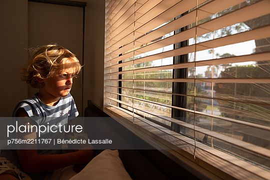 Blond boy looking out of window - p756m2211767 by Bénédicte Lassalle