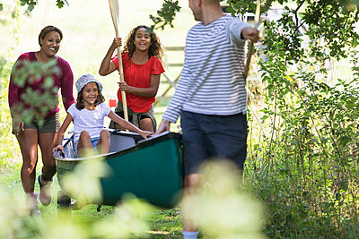 Family pulling canoe in woods - p1023m2066580 by Sam Edwards