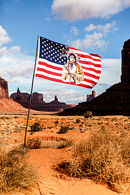 American flag with a Native American against sky on sunny day - p1094m1209072 by Patrick Strattner