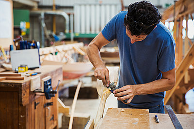 Man standing in a boat-builder's workshop, working on a wooden oar. - p1100m1490080 by Mint Images