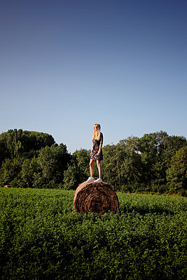 Young woman on a hay bale - p1105m2288363 by Virginie Plauchut