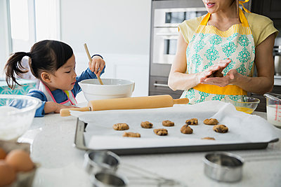 Mother and daughter baking cookies in kitchen - p1192m1006053f by Hero Images