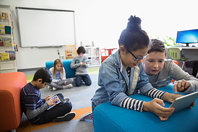 Pre-adolescent boy and girl using digital tablet in library - p1192m1231072 by Hero Images