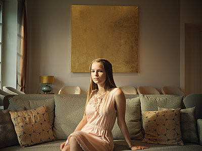 Female teenager sitting on sofa - p1376m2107371 by Melanie Haberkorn