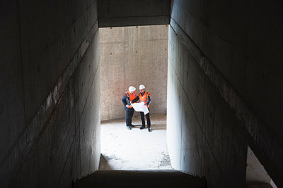 Two men with plan wearing safety vests talking in building under construction - p300m1460242 by Daniel Ingold