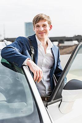 Portrait of smiling businessman at car - p300m1580993 by Uwe Umstätter