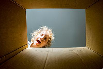 Surprised blond boy looking in cardboard box - p300m2277124 by Irina Heß
