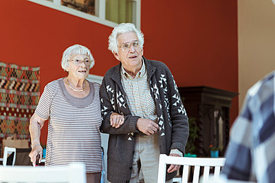 Senior couple standing arm in arm at nursing home - p426m2072562 by Kentaroo Tryman