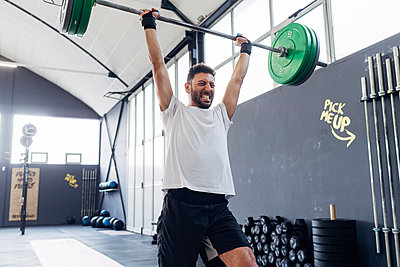 Man weightlifting barbell in gym - p429m1569283 by Eugenio Marongiu