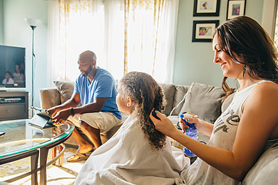 Mother styling hair for daughter in living room - p555m1306257 by Inti St Clair