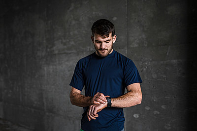 Young male runner checking smartwatch in underpass - p924m2074752 by JFCreatives
