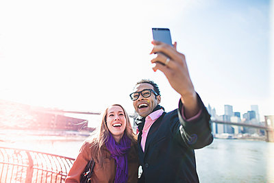 Young couple taking selfie with Brooklyn Bridge, New York, USA - p924m930576f by Chad Springer
