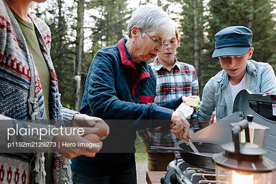 Multi-generation family, preparing food on camping stove - p1192m2129273 by Hero Images