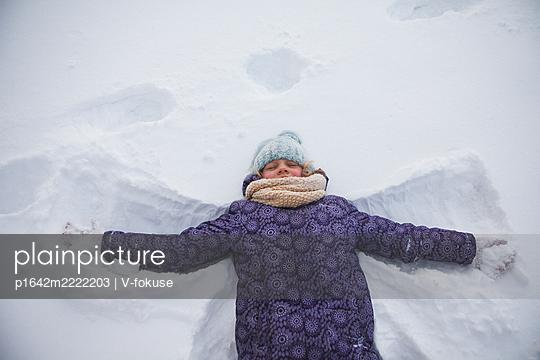 Mädchen in warmer Kleidung liegt im Schnee - p1642m2222203 von V-fokuse
