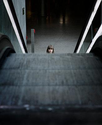 Junge Frau mit Kapuzenjacke unten an Rolltreppe im Bahnhof - p1212m1137056 von harry + lidy
