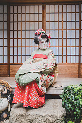 A woman dressed in the traditional geisha style wearing a kimono  - p1345m2055577 by Alexandra Kern