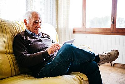 Senior man sitting on couch using tablet - p300m1206047 by Josep Rovirosa