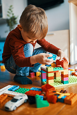 Little boy playing with building bricks on the floor at home - p300m1581602 by Zeljko Dangubic