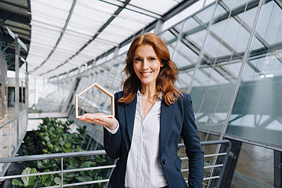 Portait of a confident businesswoman holding a house model in office - p300m2156346 by Joseffson