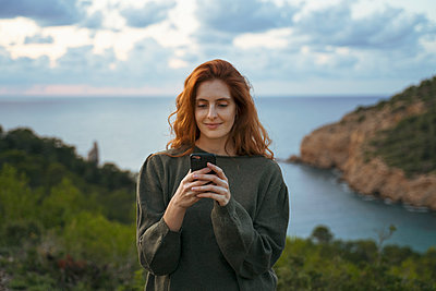 Redheaded young woman using cell phone at the coast, Ibiza, Spain - p300m2159910 by VITTA GALLERY