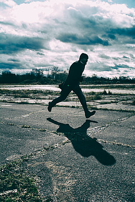 Silhouetted male figure running  - p794m1476579 by Mohamad Itani