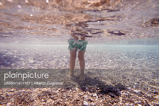Underwater view of Caucasian girl standing in ocean - p555m1411181 by Alberto Guglielmi