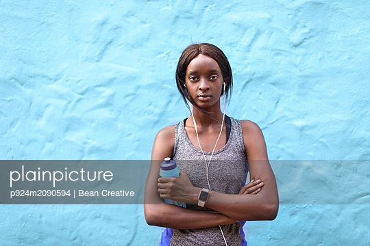 Young female runner in front of turquoise wall, waist up portrait - p924m2090594 by Bean Creative