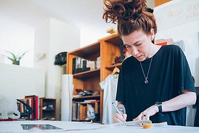 Fashion designer working in her studio - p429m2058363 by Eugenio Marongiu