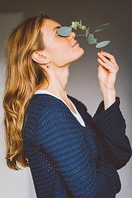 Junge Frau mit Eukalyptus-Blüte in der Hand - p432m2229723 von mia takahara