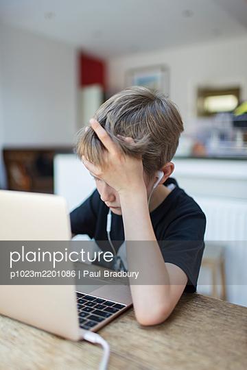 Boy with headphones homeschooling at laptop - p1023m2201086 by Paul Bradbury