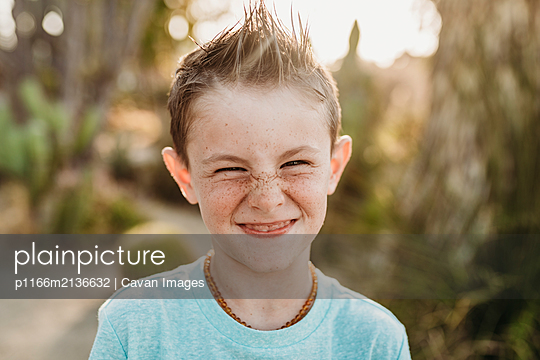 Close up portrait of cute young boy with freckles smiling - p1166m2136632 by Cavan Images