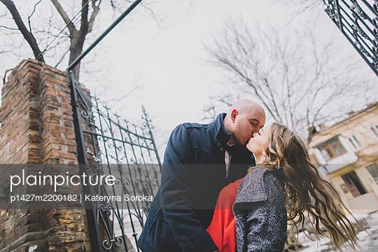 Newlywed couple kissing on street - p1427m2200182 by Kateryna Soroka