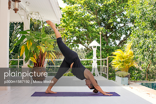 Woman practicing yoga on terrace at the poolside - p300m1587192 von Mosu Media