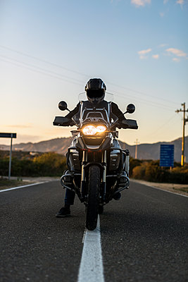Lonely biker riding on an empty road - p1165m1541058 by Pierro Luca