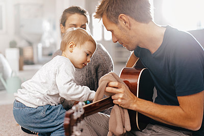Little girl examining father's guitar at home - p300m1535987 by Kniel Synnatzschke
