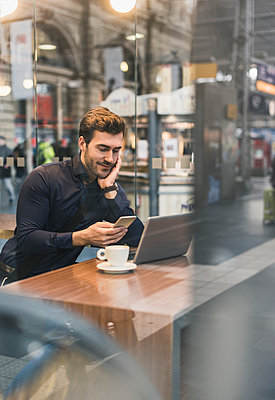 Young businessman in a cafe at train station with cell phone and laptop - p300m1562881 by Uwe Umstätter