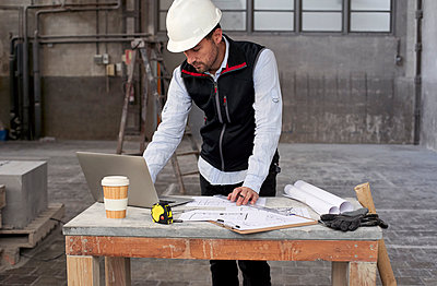 Male architect with blueprints using laptop on table while standing in building - p300m2243429 by Veam