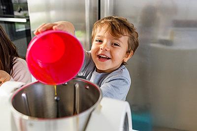 Smiling cute boy pouring egg yolk into dough mixer in kitchen - p300m2266328 by Ignacio Ferrándiz Roig