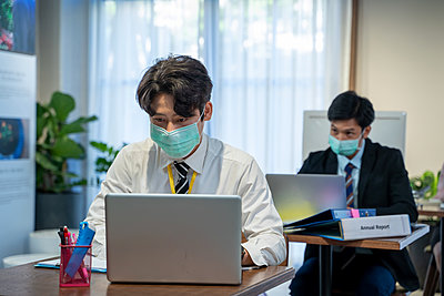 Asian business people wear protective face mask due covid workin - p1166m2246626 by Cavan Images