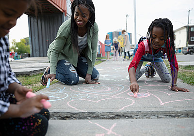 Mother and daughters coloring with sidewalk chalk - p1192m2024458 by Hero Images