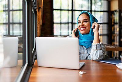 Businesswoman wearing turquoise hijab in a cafe and working with her laptop, on the phone - p300m2143608 by Eloisa Ramos