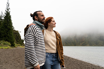 Smiling couple looking at scenic lake while enjoying vacation in Sao Miguel Island, Azores, Portugal - p300m2197220 by VITTA GALLERY