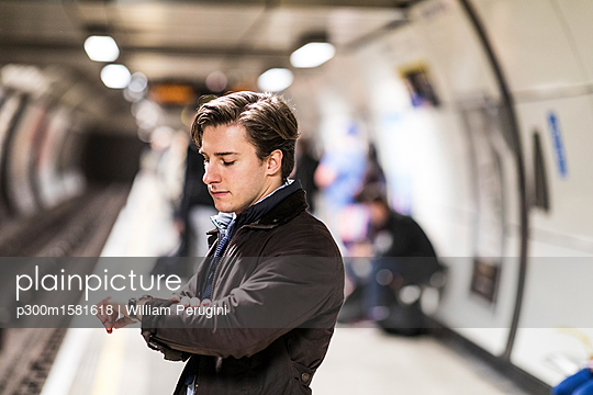 UK, London, businessman waiting at underground station checking the time - p300m1581618 von William Perugini