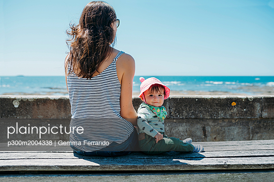 France, mother and baby girl sitting on a bench at beach promenade - p300m2004338 von Gemma Ferrando