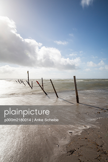 Denmark, Romo, Blavand, Long exposure of clouds over row of coastal poles - p300m2180014 by Anke Scheibe